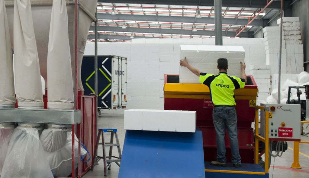 Worker guiding a waffle pod into an expanded polystyrene recycling machine